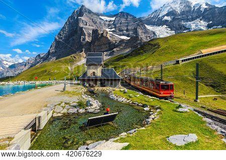 Cogwheel Red Passenger Train In The Small Mountain Station. Small Train Station On The Shore Of The