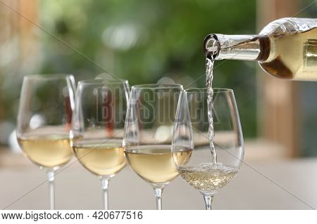 Pouring White Wine From Bottle Into Glass On Blurred Background