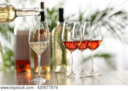 Pouring White Wine From Bottle Into Glass On Wooden Table, Space For Text