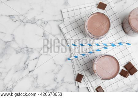 Delicious Chocolate Milk On White Marble Table, Flat Lay. Space For Text