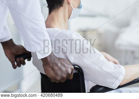 Close-up Of African Doctor Pushing The Patient While She Sitting In Wheelchair
