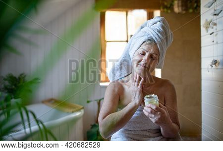 Happy Senior Woman Wrapped In A Towel In Bathroom At Home, Applying Homemade Body Moisturiser.