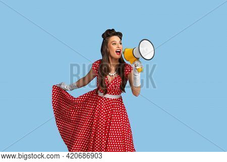 Mega Sale. Agitated Young Pinup Woman In Retro Clothes Shouting Into Megaphone On Blue Studio Backgr