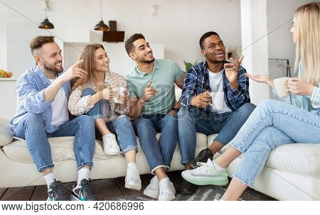 Group Of Happy Millennial Friends Drinking Tea, Having Talk, Enjoying Time Together At Home