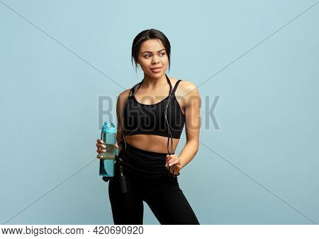 Fitness Concept. Fit African American Woman With Jump Rope And Bottle Of Water Posing Over Blue Back