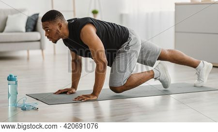 Sporty African Man Doing Running Plank Exercise At Home, Side-view