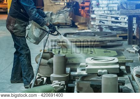 Woman Worker Sprays Special Molds For Smelting Metal Parts In Foundry Workshop.