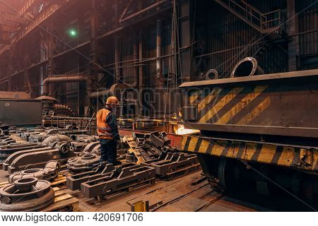 Foundry Worker In Workshop With Cast Finished Metal Products Smelted At Steel Mill Plant.
