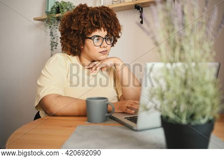 Attractive Happy Stylish Plus Size African Black Woman Student Afro Hair In Glasses Studying Online