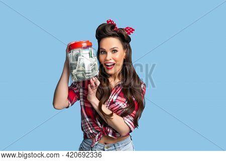 Portrait Of Posh Pinup Lady Holding Jar Full Of Money On Blue Studio Background