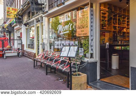 Amsterdam, Netherlands - 20 April, 2021: Street Bench With Striped Tape As Measure Of Social Distanc