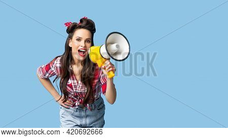 Cheerful Pinup Woman In Retro Style Clothes Making Announcement With Megaphone On Blue Studio Backgr