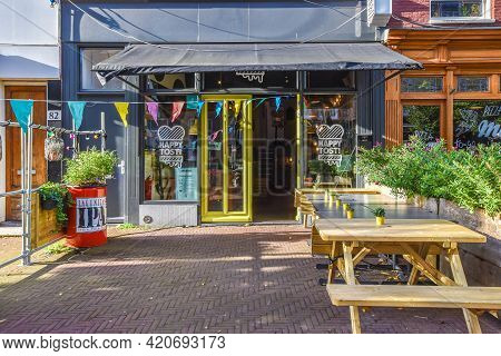 Amsterdam, Netherlands - 20 April, 2021: Exterior Design Of Cozy Restaurant With Wooden Tables And B