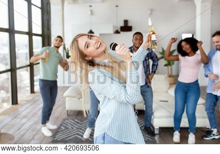 Positive Millennial Blonde Lady With Bottle Of Beer Singing Karaoke While Having Party With Her Frie