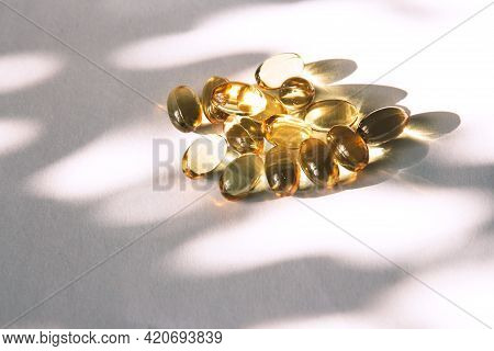Shiny Yellow Fish Oil Capsules On A Light Background With Shadows Of Focus On The Table. Vitamin E.