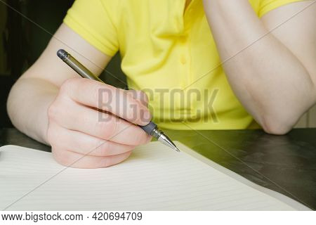 Close-up Of Female Hands With Pen And Notepad. Woman Makes Notes In The Workbook. Student Prepares F