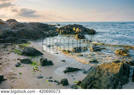 Sea Beach In The Morning. Boulders On The Sandy Shore Washed By Calm Water. Few Clouds On The Bright