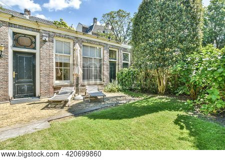 Amsterdam, Netherlands - 22 May, 2020: Bright Greenery Of Lawn And Trees In Yard Of Aged Stone House