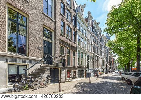 Amsterdam, Netherlands - 22 May, 2020: Stone Facades Of Traditional Dutch Medieval Buildings In Row