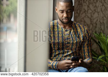 Portrait Of Black African Business Man And Entrepreneur Sitting On Window Sill Looking Looking Down