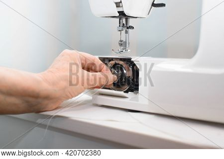 Preparing An Electric Sewing Machine For Work. A Woman's Hand Installs A Bobbin Into The Sewing Equi
