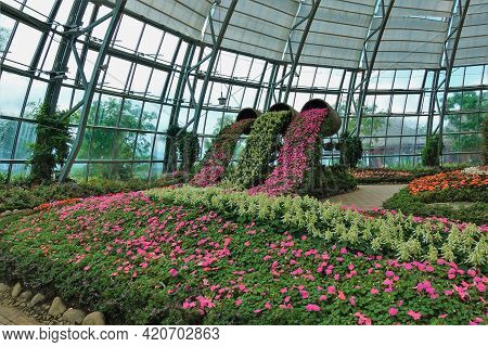 The Flower Bed In The Park Is Covered With A Transparent Dome. The Composition Of Bright Flowers Is