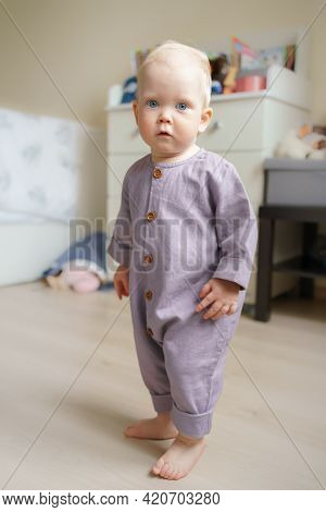 Sweet Blue Eyed Infant Wearing Cute Outfit Looking At Camera While Enjoying Playtime In Bright Kids