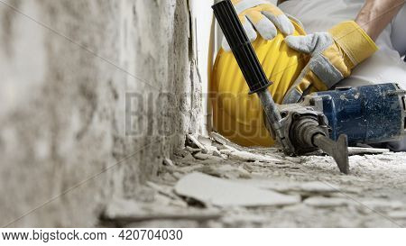 House Renovation Concept, Construction Worker Holds In Hands Helmet, Close Up With Jackhammer And Wa