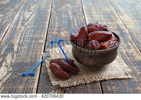 Dried Dates Fruit In Ceramic Bowl On Old Wooden Table. Highly Valuable Food Product.