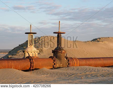 An Old Rusty Oil Pipeline In The Desert With Valves. Pipeline For Oil Or Gas At Dawn. Mining Of Natu