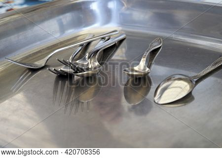 Spoons And Forks See Themselves. Shadows. Selective Focus On Spoons And Forks In Bloored Tray Backgr