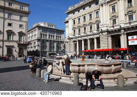 Rome, Italy - April 10, 2012: People Sit By The Fountain At Piazza Colonna Square In Rome. According