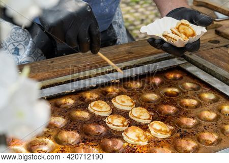 Man Serving The Dutch Specialty Poffertjes From An Outdoor Griddle