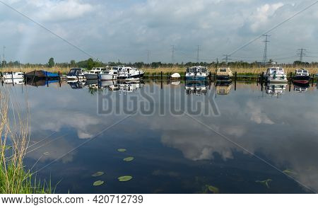 Alblasserdam, Netherlands - 14 May, 2021: Colorful Boats Moored In The Canals Of South Holland