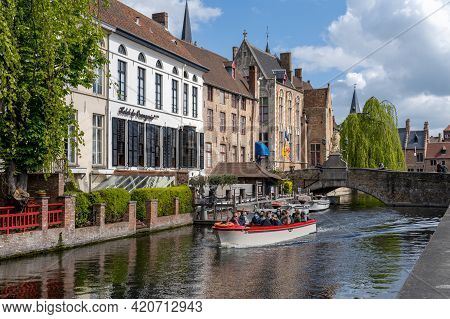 Tourists Enjoy An Idyllic Boat Tour On The Canals In The Historic City Center Of Bruges