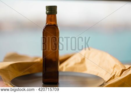 A Glass Brown Transparent Faceted Bottle Full Without Labels With Vegetable Oil Stands On A Black Pl