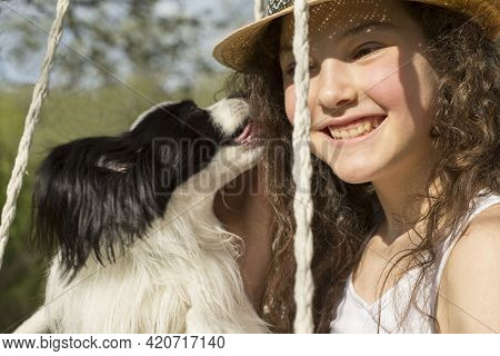Summer, Emotions. A Girl In A Hat Smiles At Her Dog. A Girl Plays With A Papellon. The Girl Enjoys A