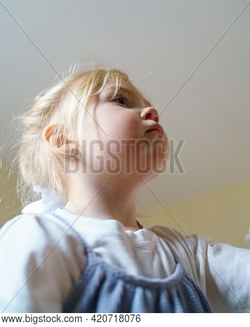 Bottom View Of Sweet Little Girl With Blonde Hair Staring At Something While Spending Free Time At H