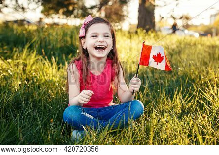 Adorable Cute Happy Caucasian Girl Holding Canadian Flag. Smiling Child Sitting On Grass In Park Hol