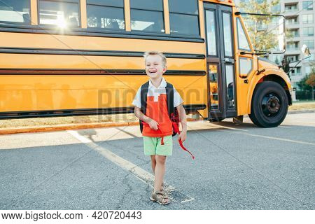 Happy Smiling Caucasian Boy Elementary Student With Backpack Near Yellow Bus On First September Day.