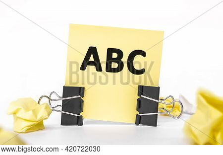 Text Abc On A Yellow Piece Of Paper For Notes. Stationery Paper Clips, Crumpled Paper. Financial Bus