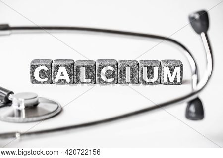 Stone Block Form Word Calcium With Stethoscope. White Background. Medical Concept. Mineral, Body Nee