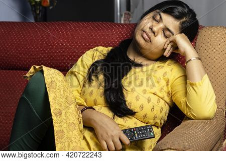 An Middle Aged Indian Woman In Yellow Dress Taking Nap On Sofa With Tv Remote In Hand