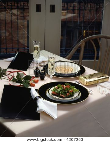 Restaurant Table Setting With Linen Tablecloth And Champagne