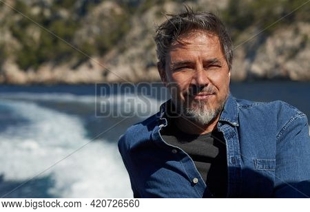 Portrait of mature age, middle age, mid adult man in 50s, happy confident smile. Outdoor, sailor, boat, sunglasses, sea.