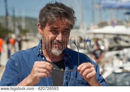 Portrait of mature age, middle age, mid adult man in 50s, happy confident smile. Outdoor, sailor, boat, sunglasses.