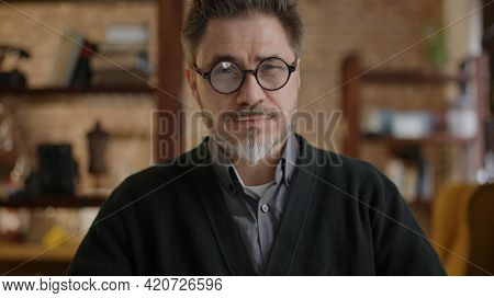 Happy bearded older man at home wearing glasses looking at camera, smiling. Portrait of mature age, middle age, mid adult man in 50s.