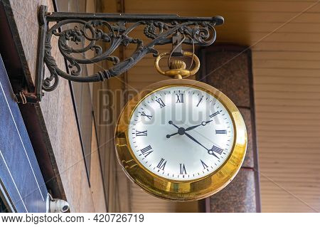 Golden Clock With Illuminated White Dial Hanging