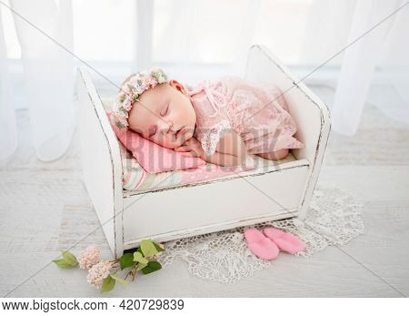 Newborn baby girl wearing cute costume sleeping in the little designed bed and holding her hands under cheek. Beautiful infant child napping lying on her tummy. Pretty kid resting in light room