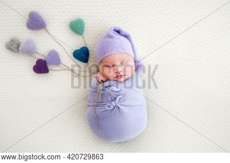 Newborn baby girl swaddled in light blue fabric sleeping and holding in her hands knitted colorful hearts. Little cute infant child napping in beautiful composition. Adorable kid wearing hat resting
